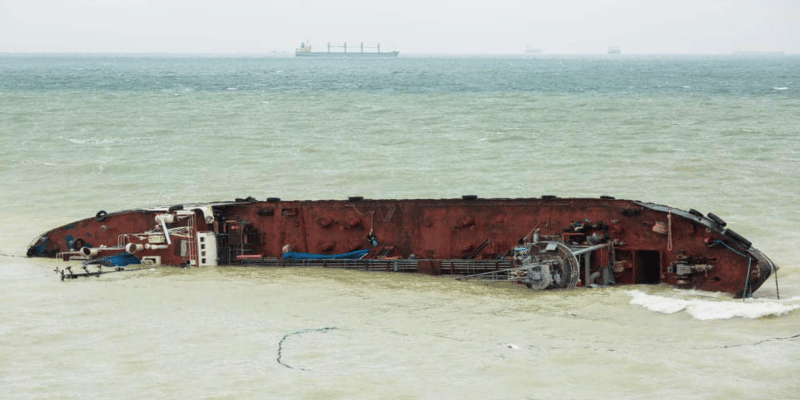 Cargo ship on its side in the ocean sinking